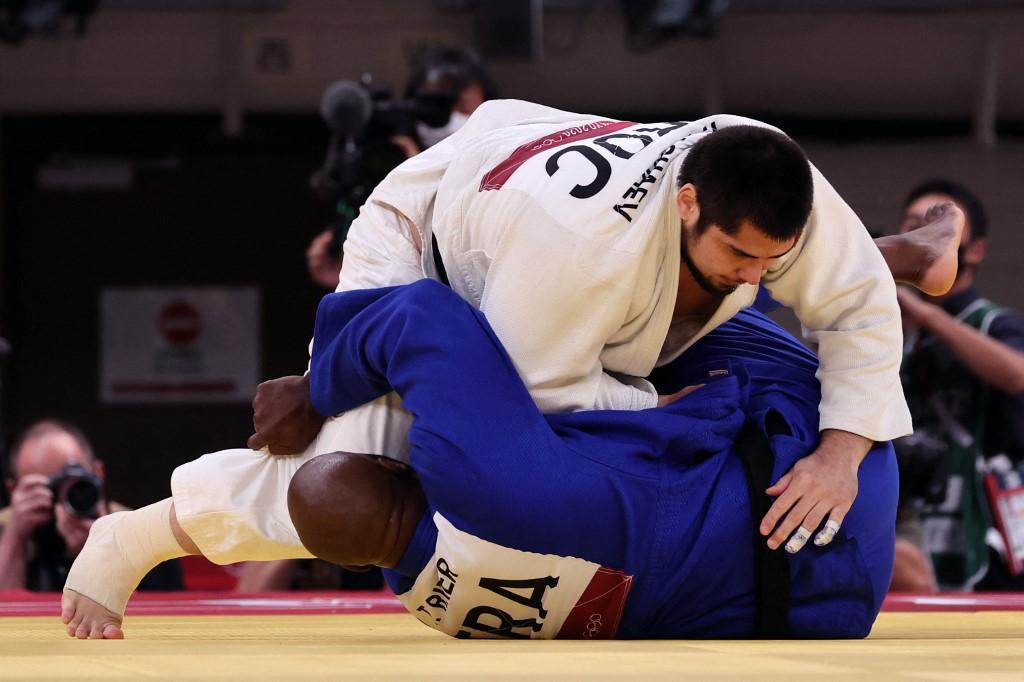 Le Français Teddy Riner (bleu) et le Russe Tamerlan Bashaev s'affrontent en quart de finale de judo hommes +100kg lors des Jeux Olympiques de Tokyo 2020 au Nippon Budokan à Tokyo le 30 juillet 2021. (Photo de Jack GUEZ / AFP)