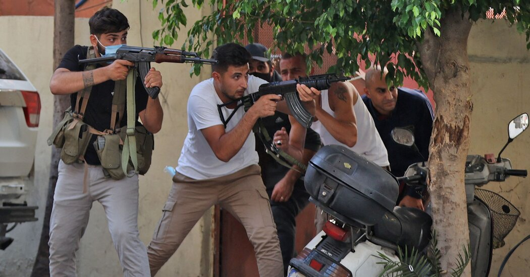 Des combattants des groupes politiques et militants musulmans chiites Hezbollah et Amal tirent lors d'affrontements à Beyrouth jeudi.Crédit…Anwar Amro/Agence France-Presse — Getty Images